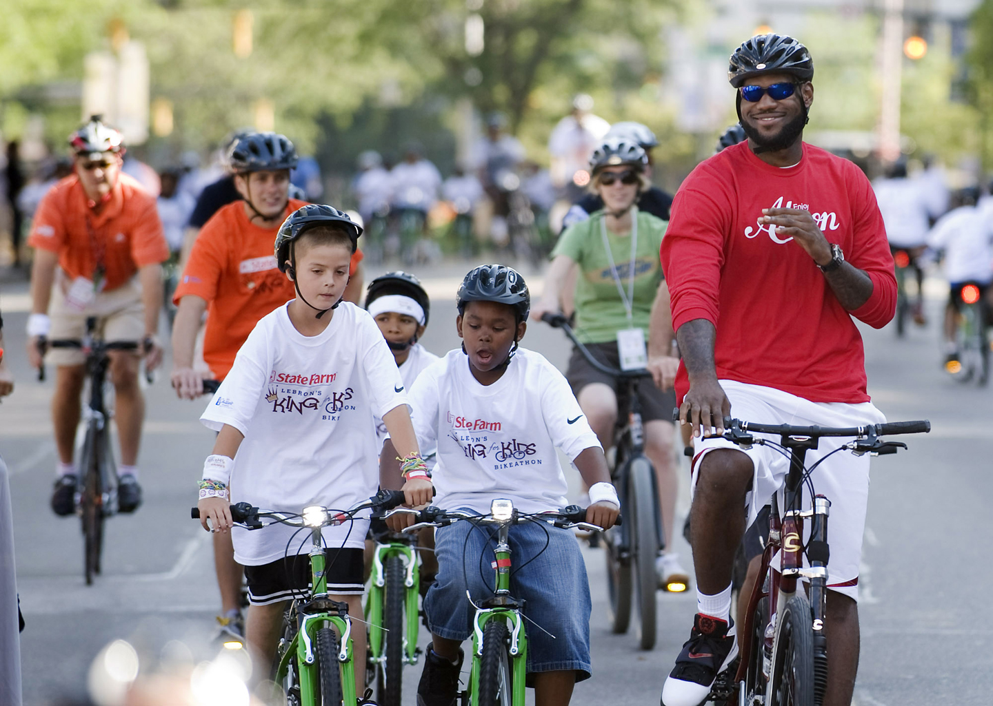 LeBron James, right, finishes his ride during the LeBron James Family Foundation, King for Kids Bike-a-thon, in Akron, Ohio, Saturday, Aug. 7, 2010.