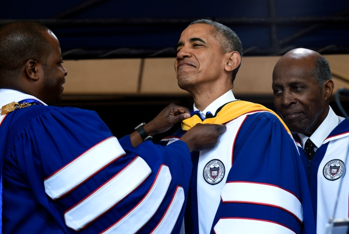 Howard University President Wayne A.I. Frederick, left, adjusts the sash of President Barack Obama, center, as he is awarded an honorary Doctor of Science degree from Howard University in Washington, Saturday, May 7, 2016, by Vernon Jordan, right. Obama was also the commencement speaker for the 2016 graduating class.