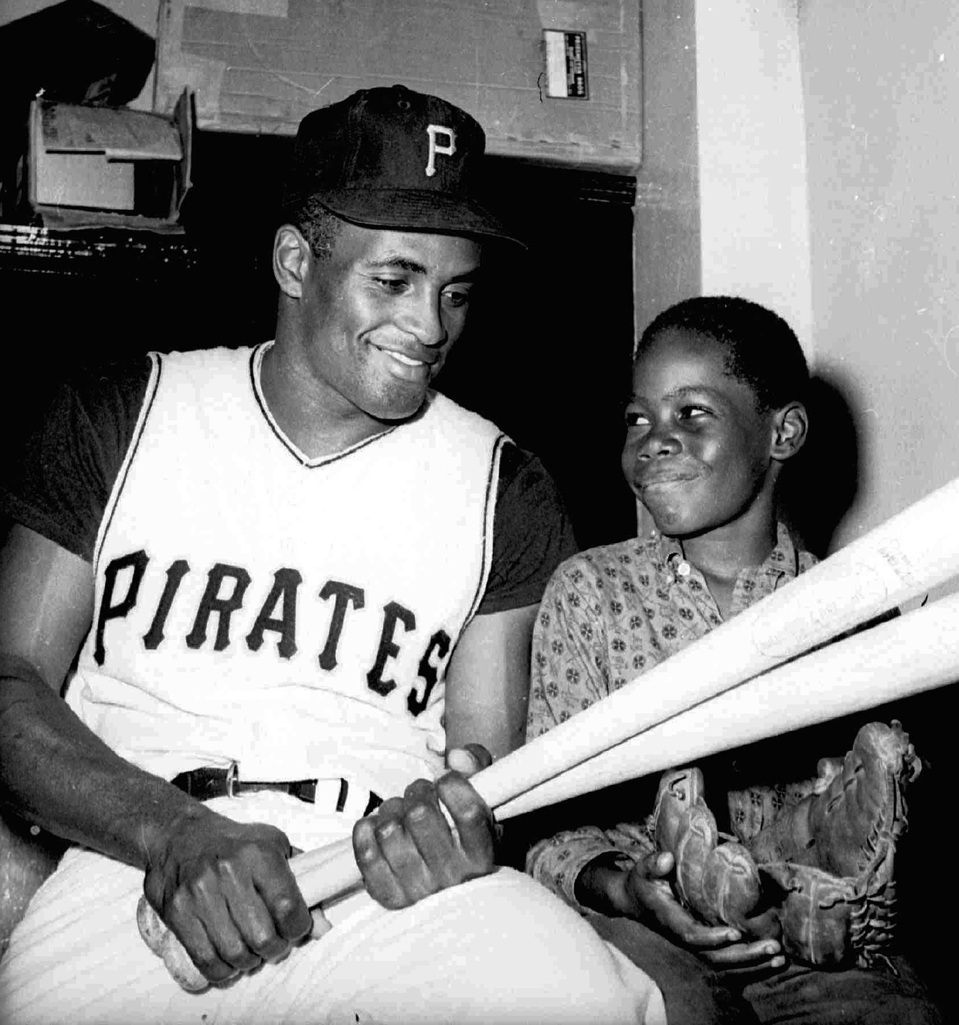Pittsburgh Pirates' Roberto Clemente shows Junior James, 9, where he likes to hit the ball, in Pittsburgh, Sept. 25, 1961.
