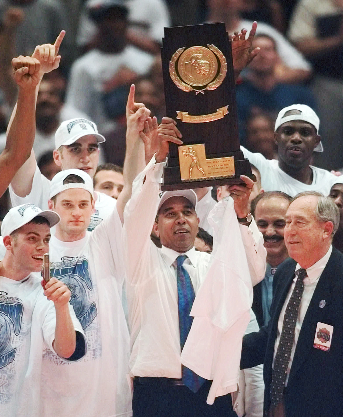 Kentucky coach Tubby Smith holds up the NCAA Div. I Championship trophy after the Wildcats 78-69 beat Utah in the NCAA Men's Final Four Championship game, Monday, March 30, 1998, at the Alamodome in San Antonio. At right is C.M. Newton, Kentucky atheletic director.