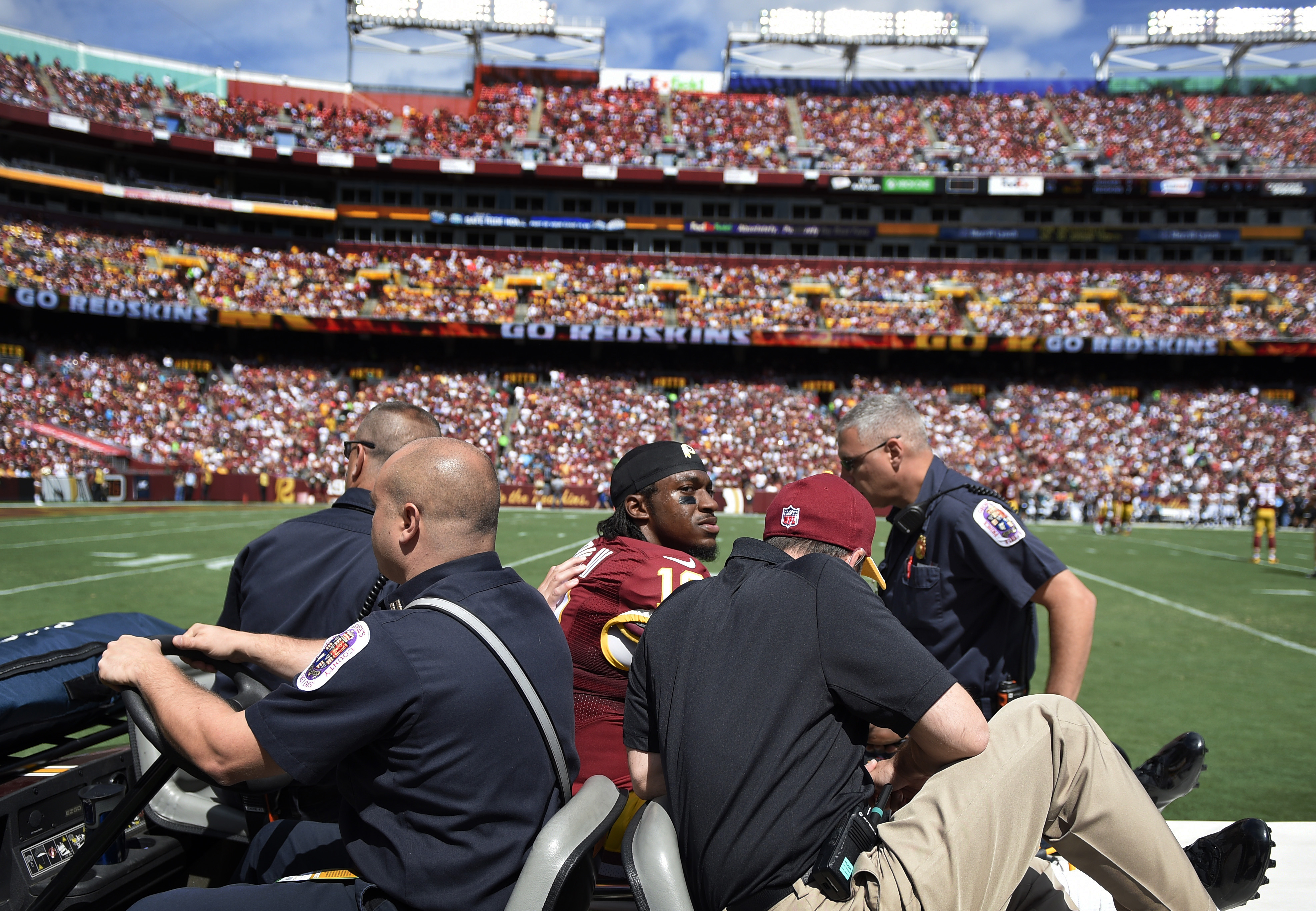 Washington Redskins quarterback Robert Griffin III (10) leaves the game on a cart after injuring his left ankle during the first half of an NFL football game against the Jacksonville Jaguars Sunday, Sept. 14, 2014, in Landover, Md. The Redskins have said Griffin will not return to the game. (AP Photo/Nick Wass)