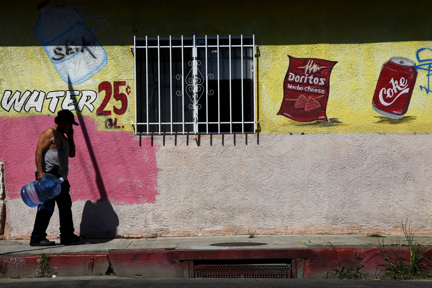 A man walks by the outside of the El Rinconcito Water Mart with a fresh jug of water. The business, with hand painted icons adorning the outside walls, has expanded to sell other items as well such as snacks and sodas.