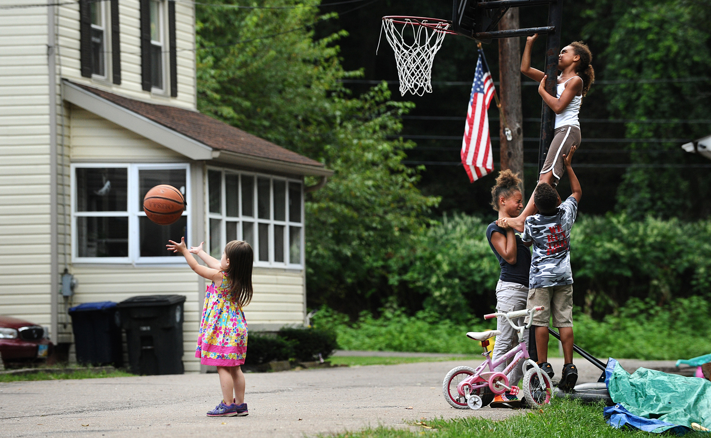 AKRON, OHIO AUGUST 27, 2014-Children team-up to adjust the the basketball rim as the former childhood home of LeBron James sits in the background on Overlook Place in Akron, Ohio. (Photo by Wally Skalij/Los Angeles Times via Getty Images)