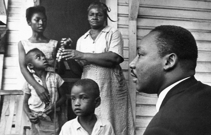 Dr. Martin Luther King Jr., right, chats with Greenwood, Mississippi residents on their front porch on July 21, 1964, during his door-to-door campaign, telling all them to register to vote and support his Mississippi Freedom Democratic party.