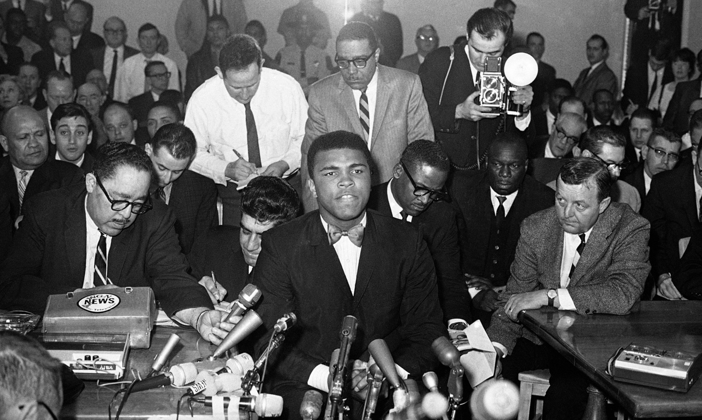 While Illinois Athletic Commission listened, heavyweight champion Muhammad Ali speaks, Feb. 25, 1966 in Chicago. He attended commission meeting as a result of Illinois Gov. Otto Kerner?s request that the commission members reconsider permission for Clay to defend title later this month. Ali had criticized his imminent army draft. (AP Photo)
