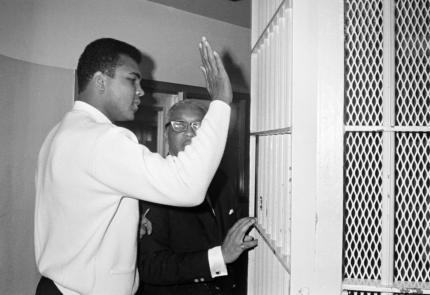 Former heavyweight boxing champ Muhammad Ali pats the bars on the door of the Dade County jail, Dec. 16, 1968, as he starts serving a 10-day sentence on an old traffic charge. Ali said this would be good training if he has to serve his five-year term for draft dodging. The former champion surrendered voluntarily today and is accompanied by his attorney Henry Arrington.