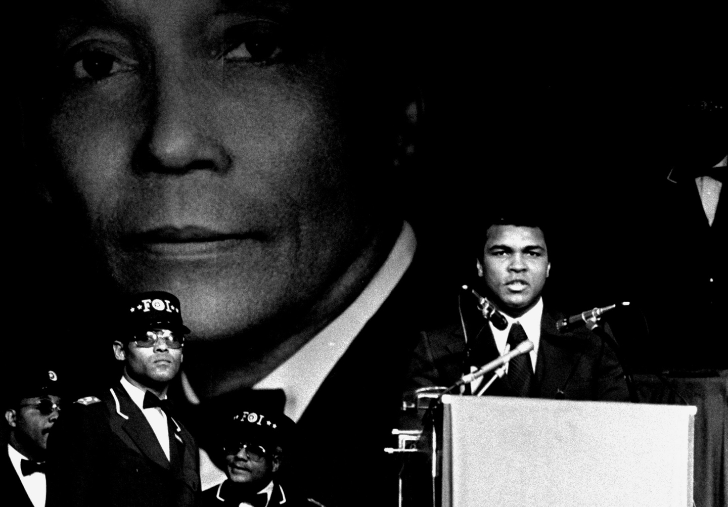 World heavyweight champion Muhammad Ali, is shown addressing a meeting of the Nation of Islam in Chicago, February 26, 1975. To the immediate left of the rostrum is Wallace Muhammad, newly chosen Spiritual Leader and Administrator of the Nation of Islam, or Black Muslims. Honorable Wallace replaces his late father, Elijah Muhammad, whose picture dominates the scene. Ceremonies took place during Muslim Savior Day.