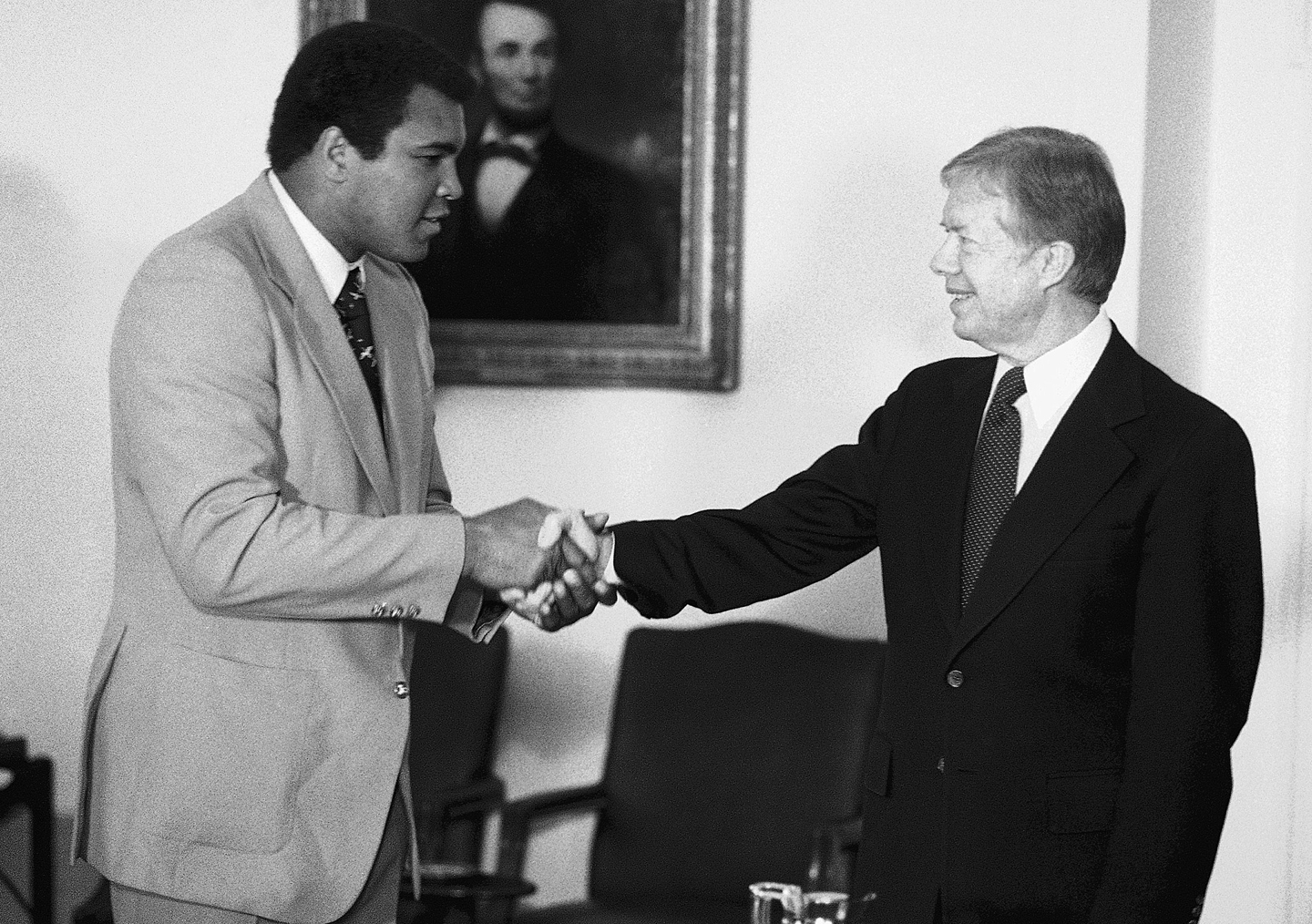 Retired heavyweight boxer Muhammad Ali, left, gives President Carter a big handshake in the Cabinet Room at the White House in Washington on Monday, Feb. 11, 1980 prior to reporting to Carter on his recent trip to Africa.