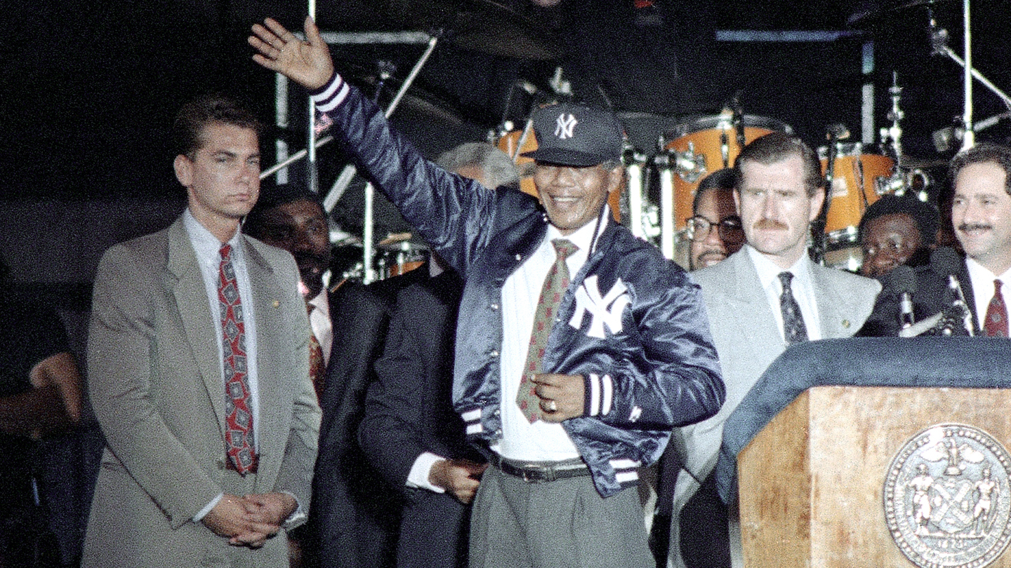 "Nelson Mandela acknowledges the crowd after donning a New York Yankees warm-up jacket and cap during a rally in his honor Thursday, June 22, 1990 at New York's Yankee Stadium. He told the crowd, ""I am a Yankee."""