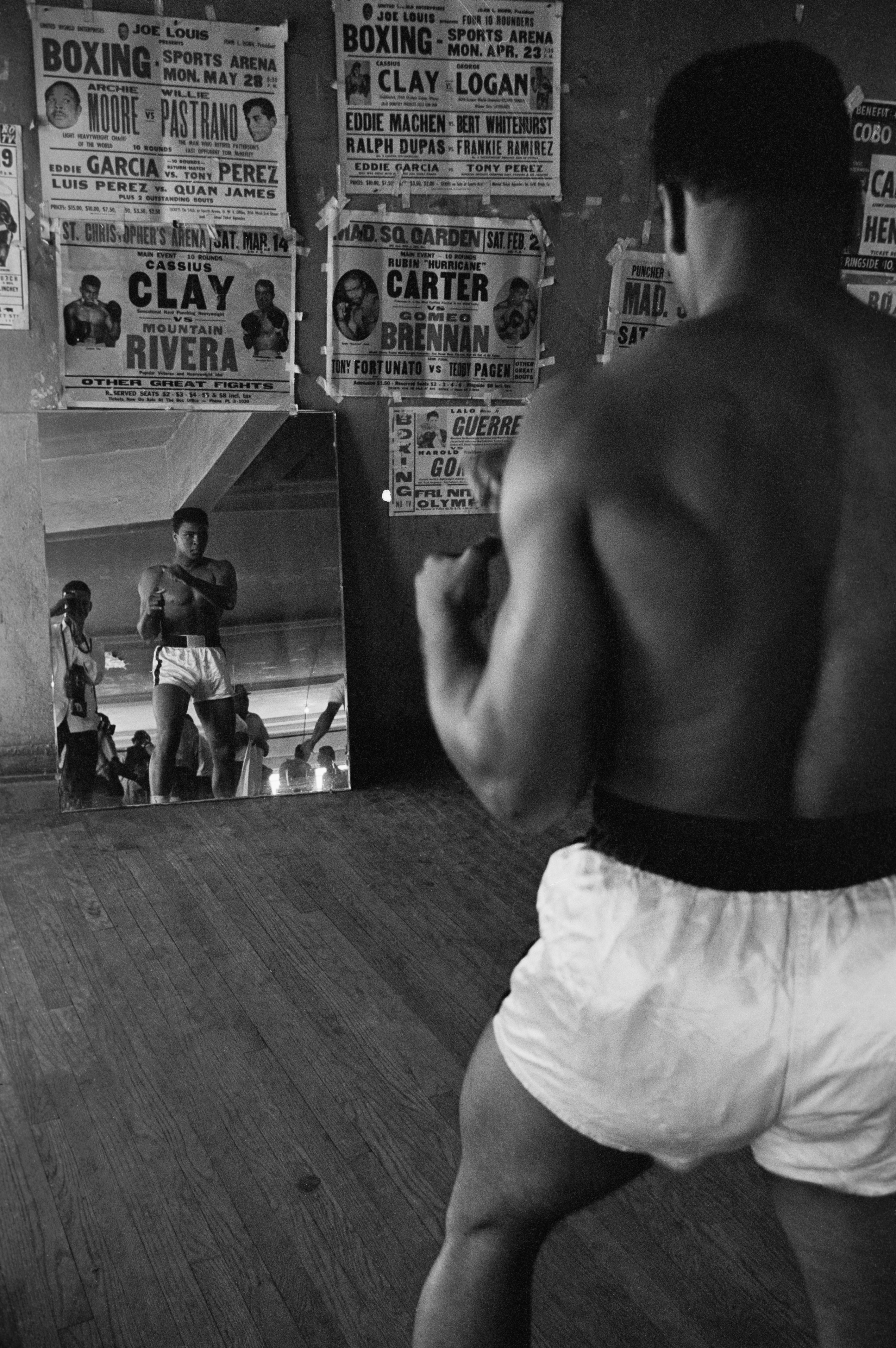 Heavyweight contender Cassius Clay watches himself in a mirror at his training gym as he prepares for a title fight with champion Sonny Liston.