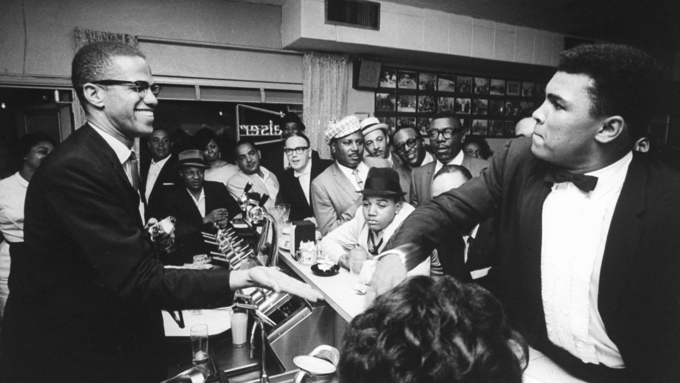March 1964 - Miami: Black Muslim leader Malcolm X (L), behind soda fountain, with tux-clad Cassius Clay (now Muhammad Ali) (R), while surrounded by jubilant fans after he beat Sonny Liston for the heavyweight championship of the world.