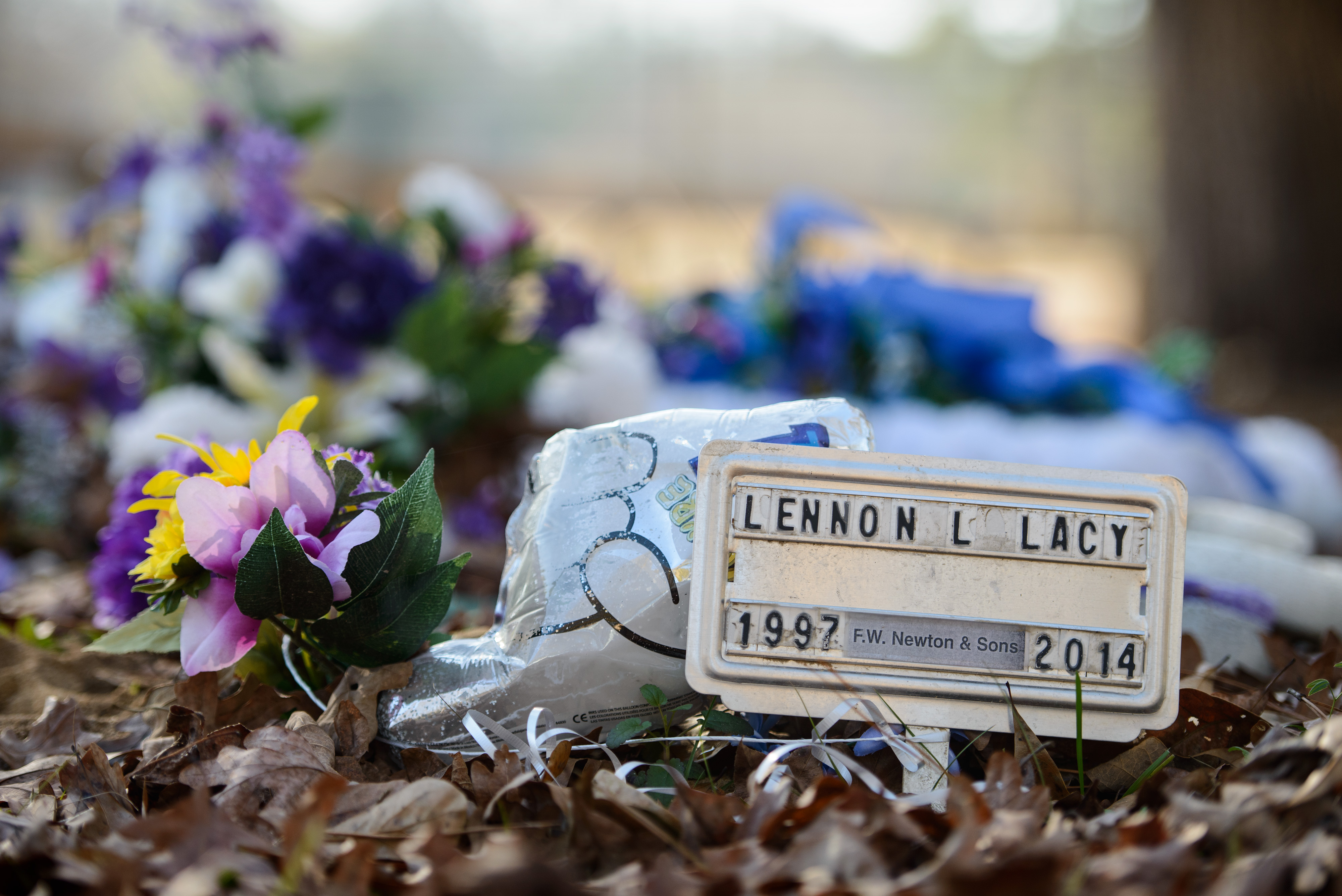 A small metal placard marks the grave of Lennon Lacy Sunday, Dec. 14, 2014, at Old Shaw-Lacy Field Cemetery in Bladenboro, N.C. Lennon Lacy, a 17-year-old black teenager, was found dead on Aug. 29, 2014, hanging from a swing set in a trailer park in the rural community. Police ruled the death a suicide, but his family believe it was murder.
