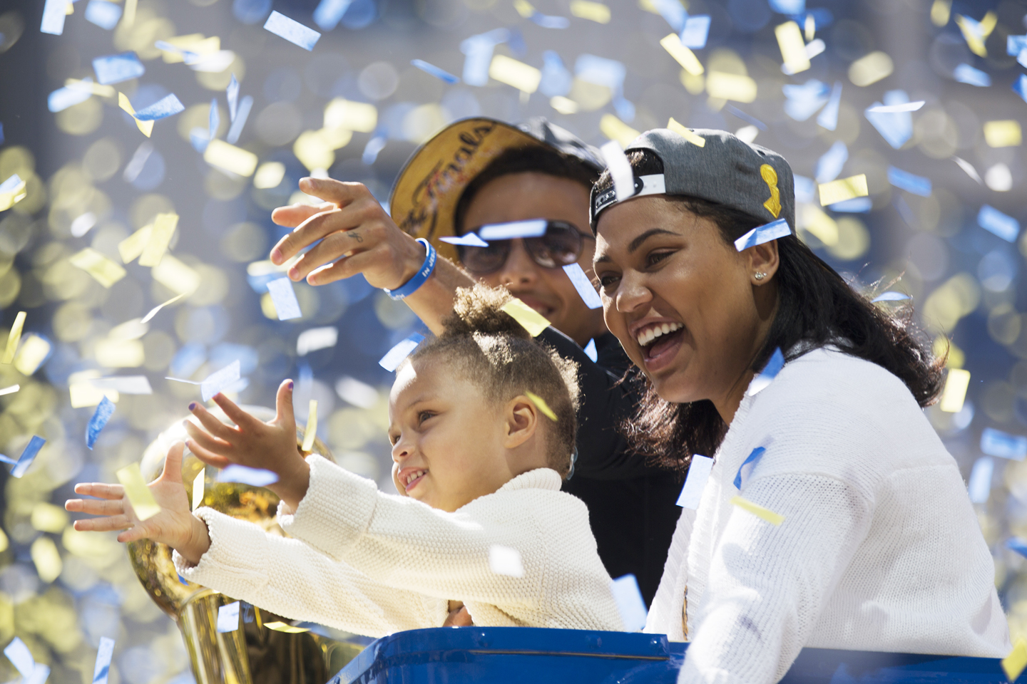Stephen Curry, daughter Riley Curry (L) and wife Ayesha Curry (R) celebrate as confetti falls during the Golden State Warriors Victory Parade in Oakland, California. Thousands are expected to attend in celebration of the Warriors' first NBA title in 40 years.