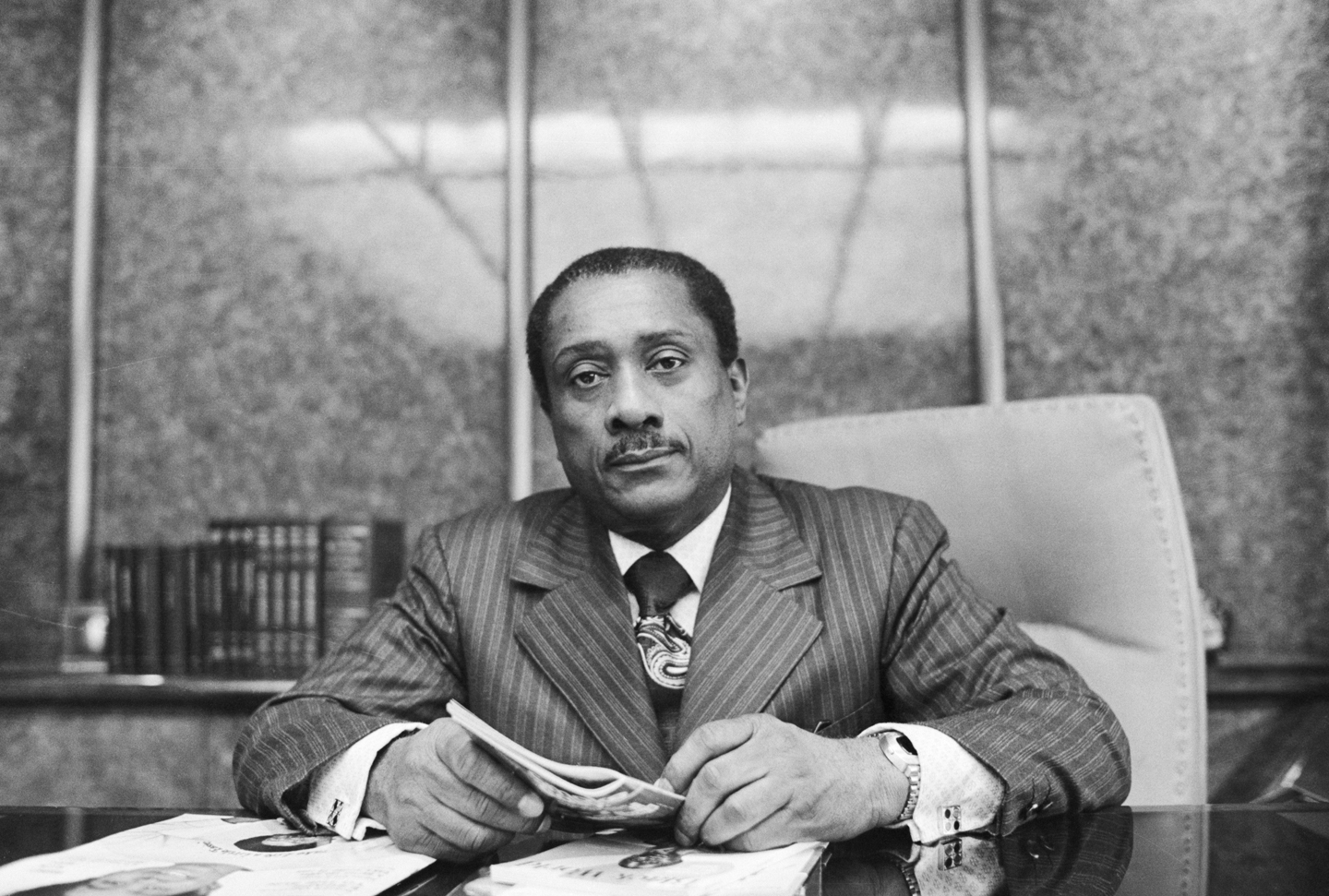 John H. Johnson, successful head of Johnson Publications Inc., a multi-million dollar corporation, selected a book from his library in his office in Chicago. From a $25 a week office boy for the Supreme Insurance Company at age of 19, he is now the Board Chairman and its largest stockholder, as well as publisher of the black-oriented magazines.