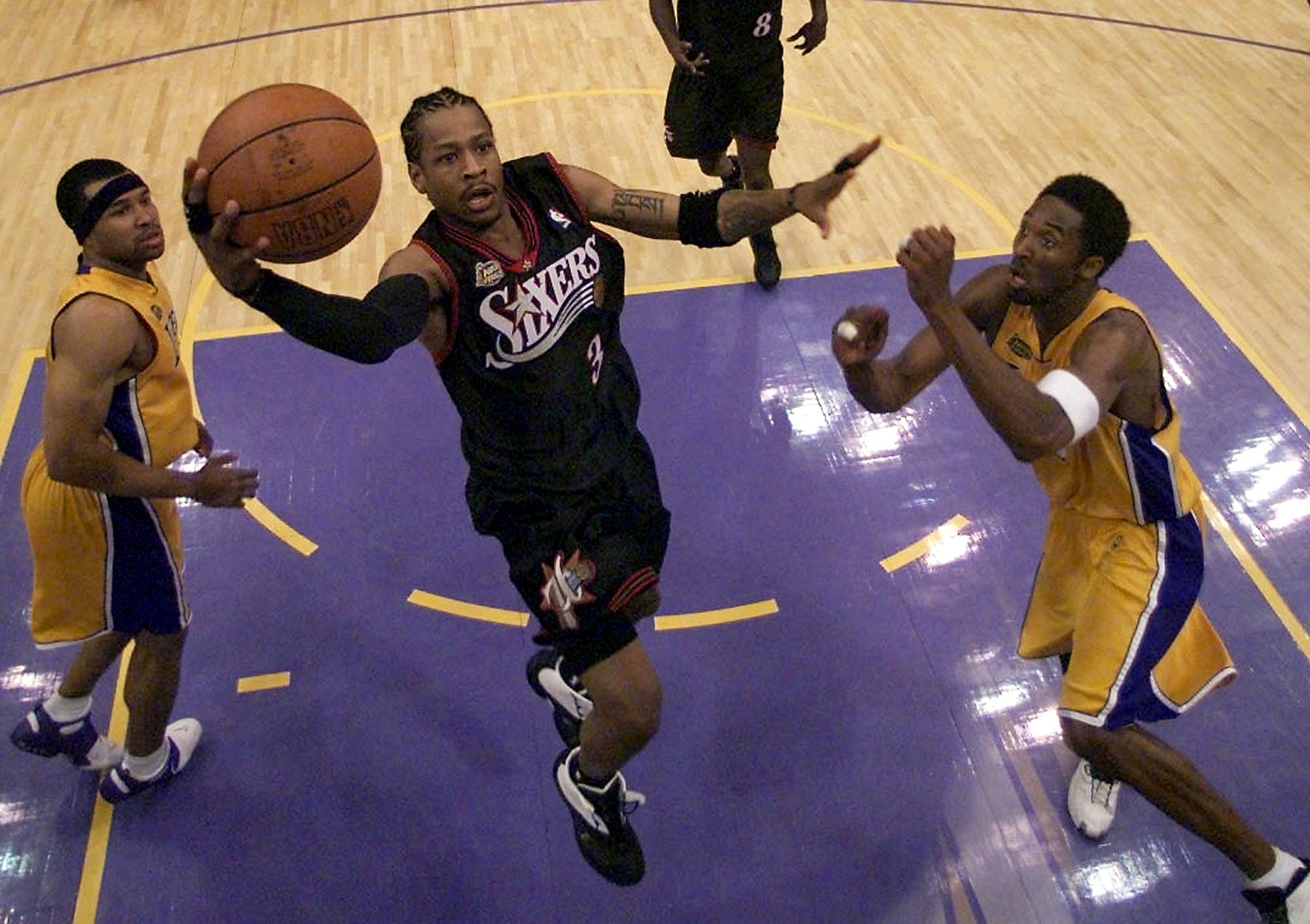 LOS ANGELES, UNITED STATES: Allen Iverson (C) of the Philadelphia 76ers goes in for a lay-up between Derek Fisher (L) and Kobe Bryant (R) of the Los Angeles Lakers 06 June, 2001 during the NBA Finals Game 1 at the Staples Center in Los Angeles. The 76ers won 107-101 in overtime to take a 1-0 lead on the best-of-seven game series. AFP PHOTO/Jeff HAYNES (Photo credit should read JEFF HAYNES/AFP/Getty Images)