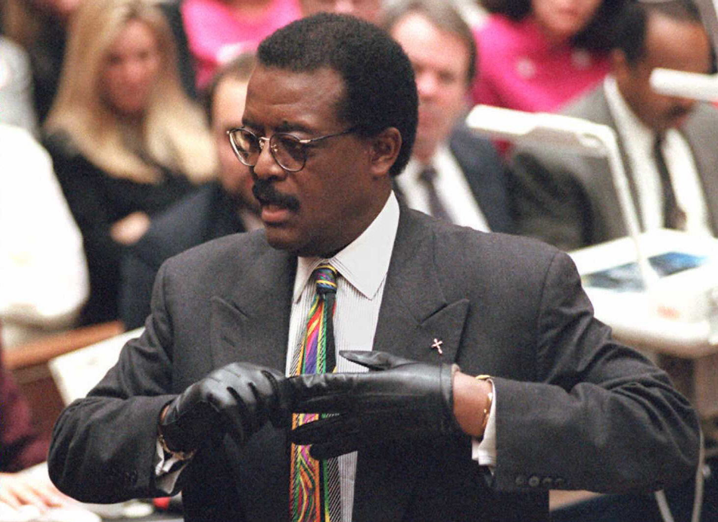 "Defense lawyer Johnnie Cochran Jr. puts on a gloves 27 September while he addresses the jury during closing arguments during the O.J. Simpson double murder trial. Cochran cited the ""defining moment in the trial"" as the day prosecutor Christopher Darden asked Simpson to try on the bloody evidence gloves and the defendant told jurors they were to small for his large hands."