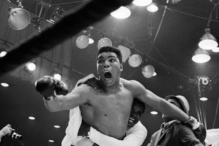 """I'm the champ!"" screams Cassius Clay as his handlers hug him joyfully after he defeated Sonny Liston for the heavyweight boxing title. Clay was credited with a 7th round TKO when Liston was unable to answer the bell because of a shoulder injury suffered in the first round."