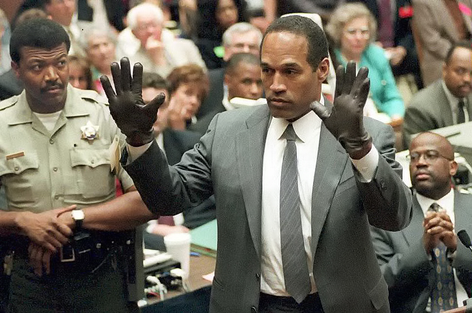 O.J. Simpson shows the jury a new pair of Aris extra-large gloves, similar to the gloves found at the Bundy and Rockingham crime scene 21 June 1995, during his double murder trial in Los Angeles,CA. Deputy Sheriff Roland Jex(L) and Prosecutor Christopher Darden (R) look on.
