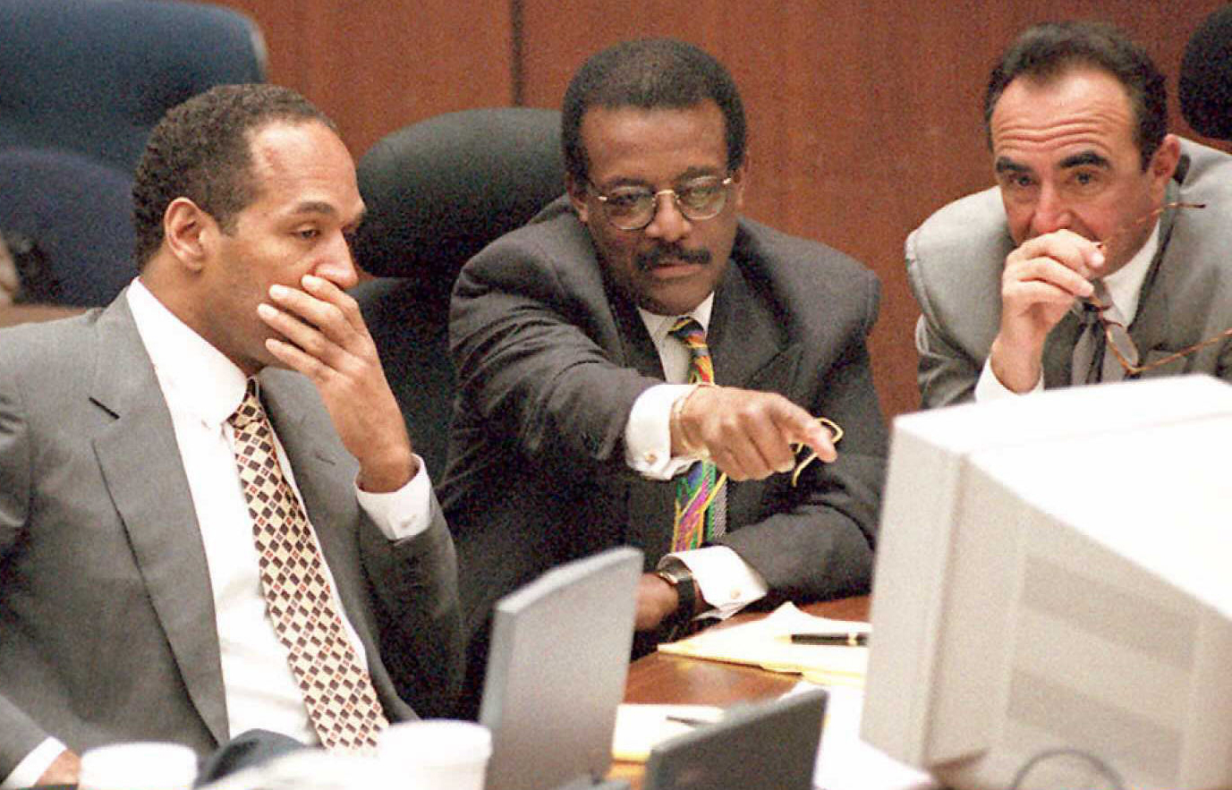 Defense Attorney Johnnie Cochran Jr. (C) points to a screen showing evidence collected at the crime scene as O.J. Simpson (L) and attorney Robert Shapiro (R) look on 11 April during the O.J. Simpson murder trial. Los Angeles police detective Dennis Fung is testifying during the morning session.