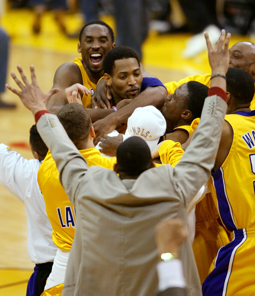 Lakers Kobe Braynt and teammates swarm Robert Horry after Horry sunk the game winning 3point shot to win Game 4 of the Western Conference Finals in Los Angeles on May 26, 2002. Kings Chris Webber looks on. (Photo by Gina Ferazzi/Los Angeles Times via Getty Images)