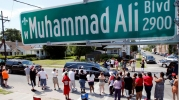 A hearse carrying the body of the late Muhammad Ali drives down Muhammad Ali Boulevard to Cave Hill Cemetery in Louisville
