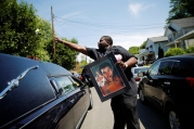A man throws a rose over the hearse carrying the remains of Muhammad Ali during the funeral procession for the three-time heavyweight boxing champion in Louisville, Kentucky, U.S.