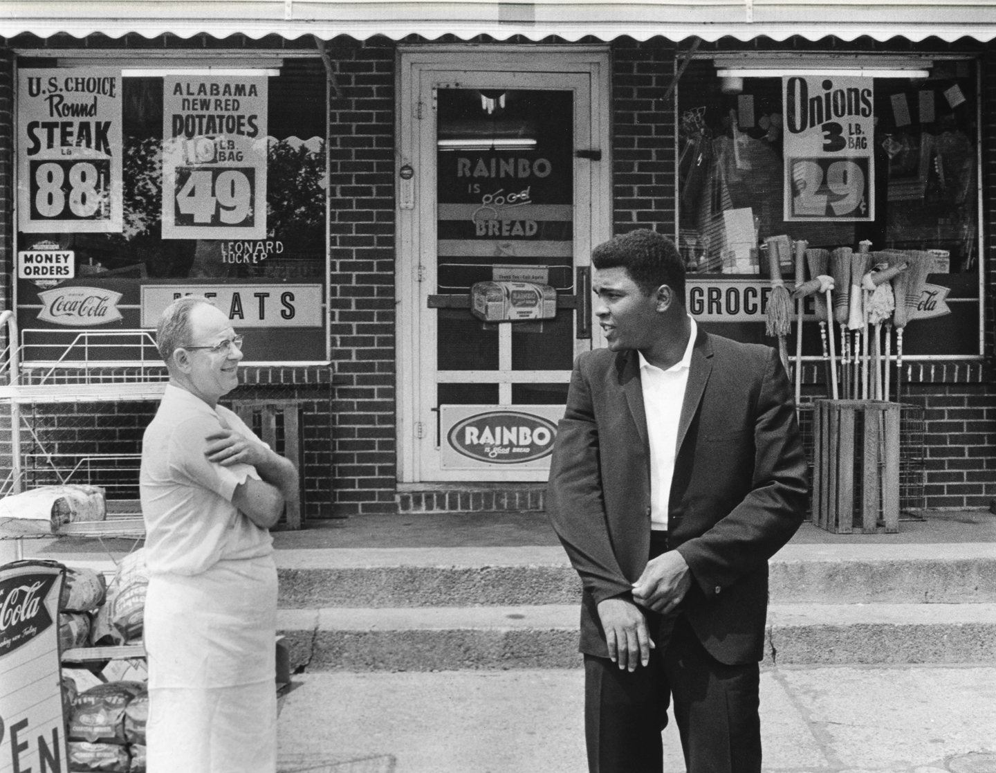 Cassius Clay aka Muhammad Ali talks with grocer Leonard Tucker outside a local grocery store.