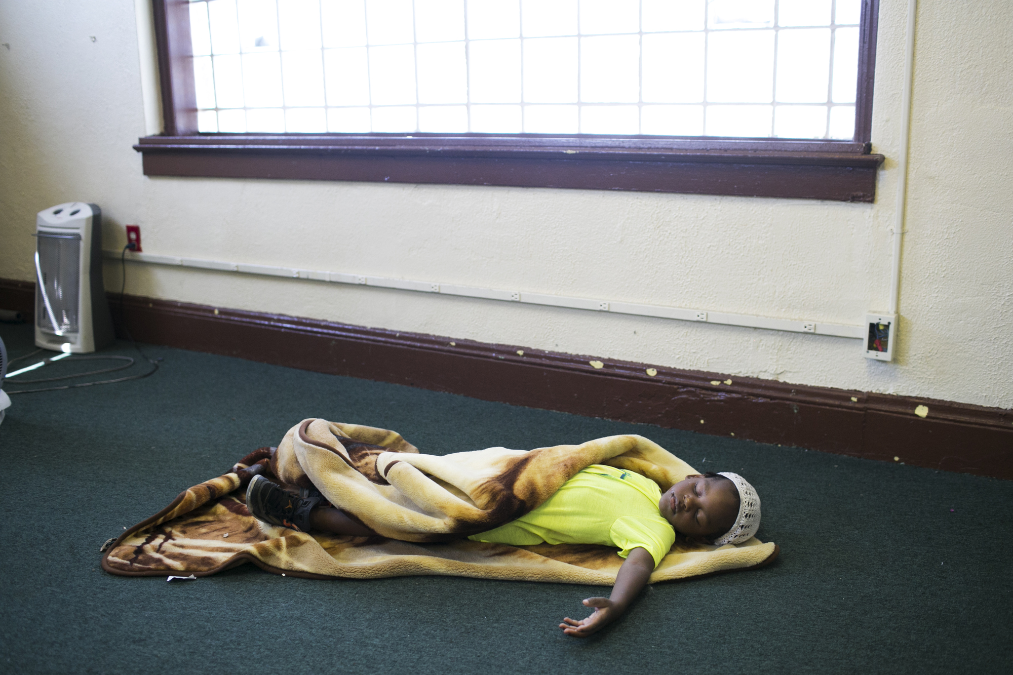 A boy sleeps on the floor of Masonic Hall in Cleveland, OH on Tuesday, July 19, 2016.