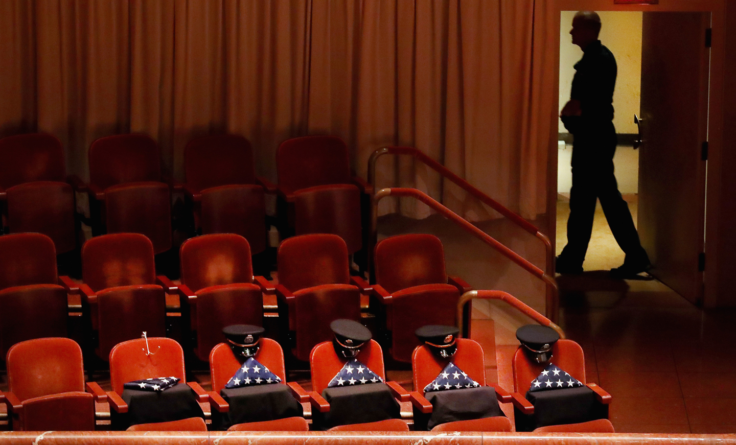 Reserved seats contain American flags and police hats during an interfaith memorial service, honoring five slain police officers, at the Morton H. Meyerson Symphony Center on July 12, 2016 in Dallas, Texas. A sniper opened fire following a Black Lives Matter march in Dallas killing five police officers and injuring 12 others.
