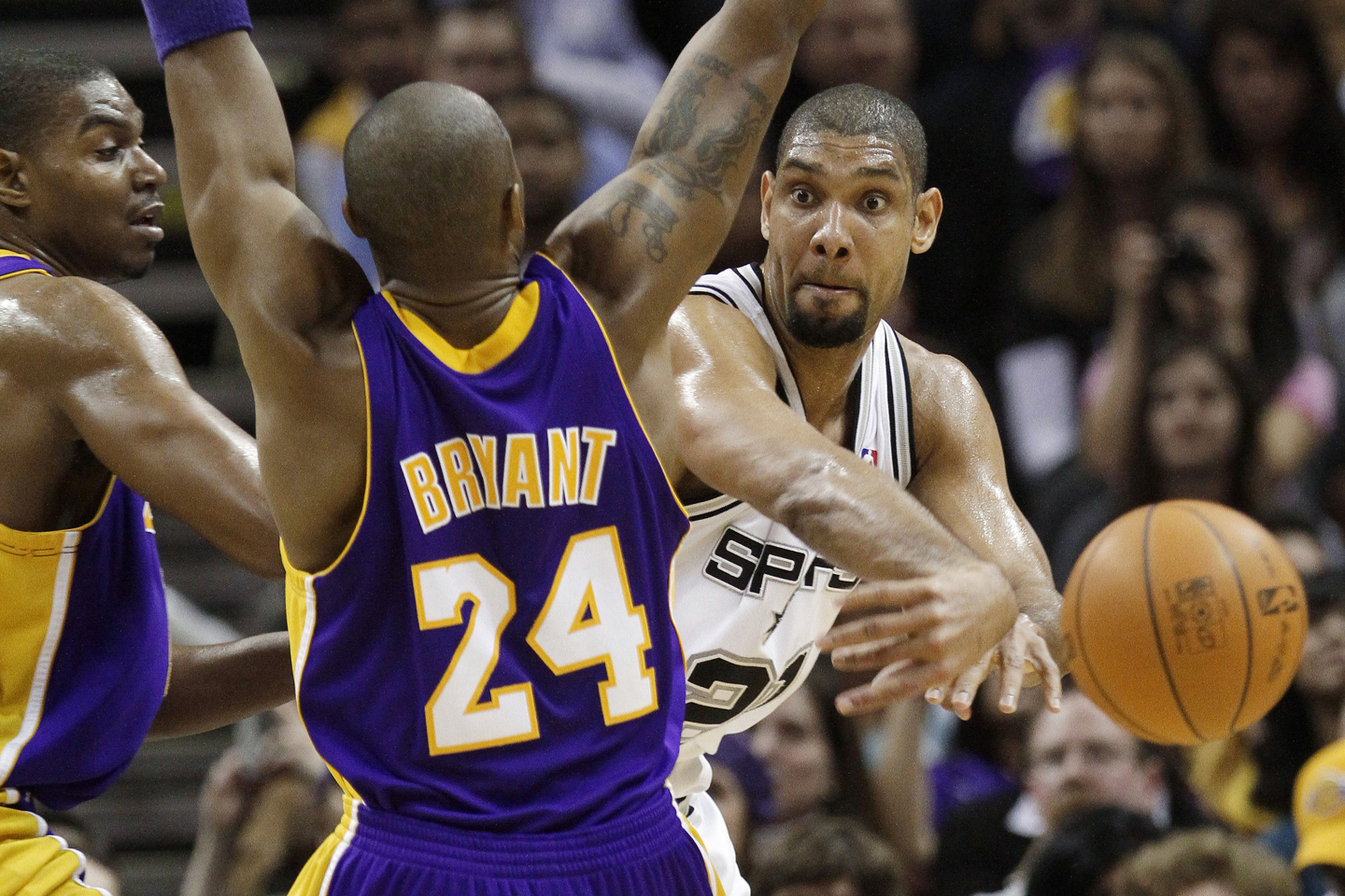 San Antonio Spurs' Tim Duncan, right, passes the ball around Los Angeles Lakers' Kobe Bryant (24) and Andrew Bynum during the third quarter of an NBA basketball game Tuesday, Jan. 12, 2010, in San Antonio. San Antonio won 105-85.