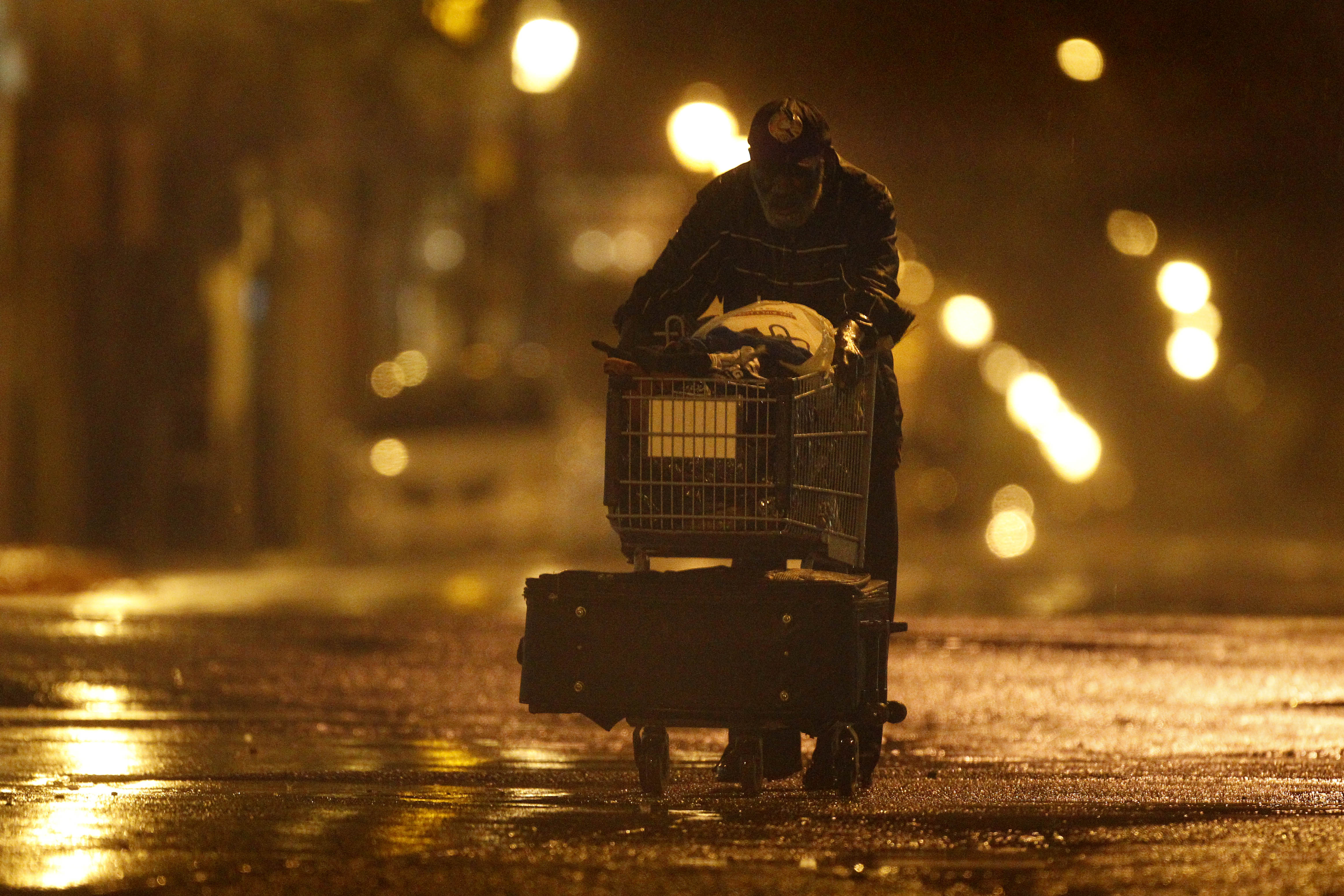 Lenard Sanders, a homeless man, pushes his cart toward a subway station to seek shelter as Hurricane Irene makes its way along the Eastern Seaboard, Sunday, Aug. 28, 2011, in Philadelphia.
