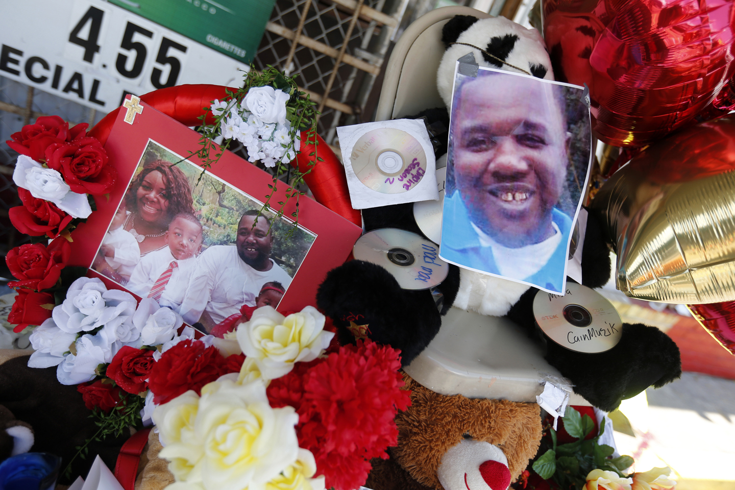 Photos of Alton Sterling are interspersed with flowers and mementos at a makeshift memorial in front of the Triple S Food Mart in Baton Rouge, La., Thursday, July 7, 2016. Sterling, 37, was shot and killed outside the convenience store by Baton Rouge police, where he was selling CDs.