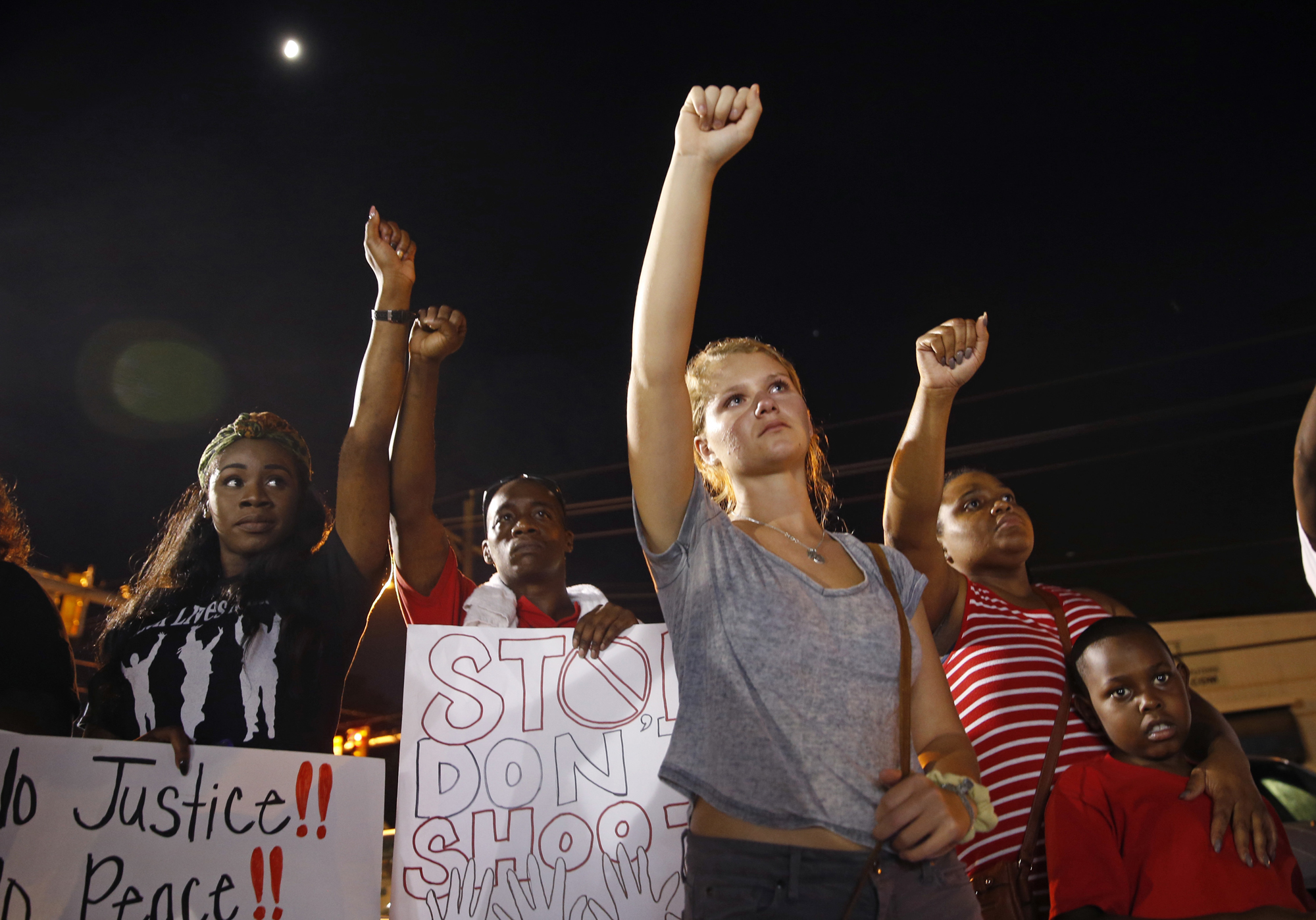 Ella Carr, center, of Austin, Texas, puts her fist up during live music at a night rally in honor of Alton Sterling, outside the Triple S Food mart in Baton Rouge, La., Monday, July 11, 2016. Sterling was shot and killed last Tuesday by Baton Rouge police while selling CD's outside the convenience store.