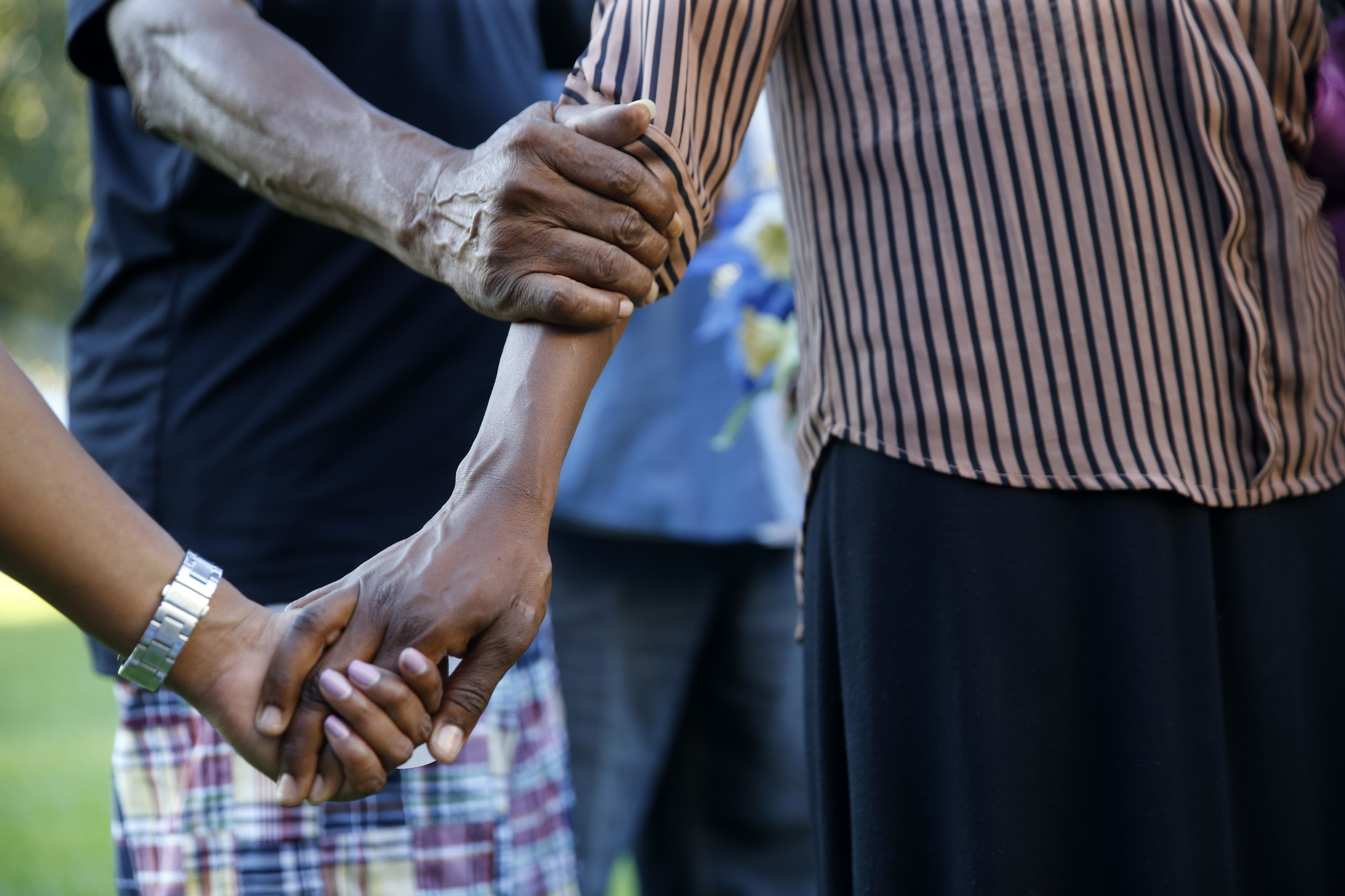 People hold hands in prayer at a candlelight vigil for Baton Rouge police officer Montrell Jackson, outside Istrouma High School, where he graduated in 2001, in Baton Rouge, La., Tuesday, July 19, 2016.