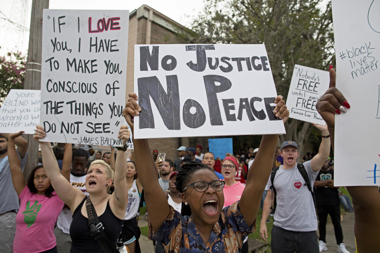 Police and protesters demonstrate in a residential neighborhood in Baton Rouge, La. on Sunday, July 10, 2016. After an organized protest in downtown Baton Rouge protesters wondered into residential neighborhoods and toward a major highway that caused the police to respond by arresting protesters that refused to disperse.
