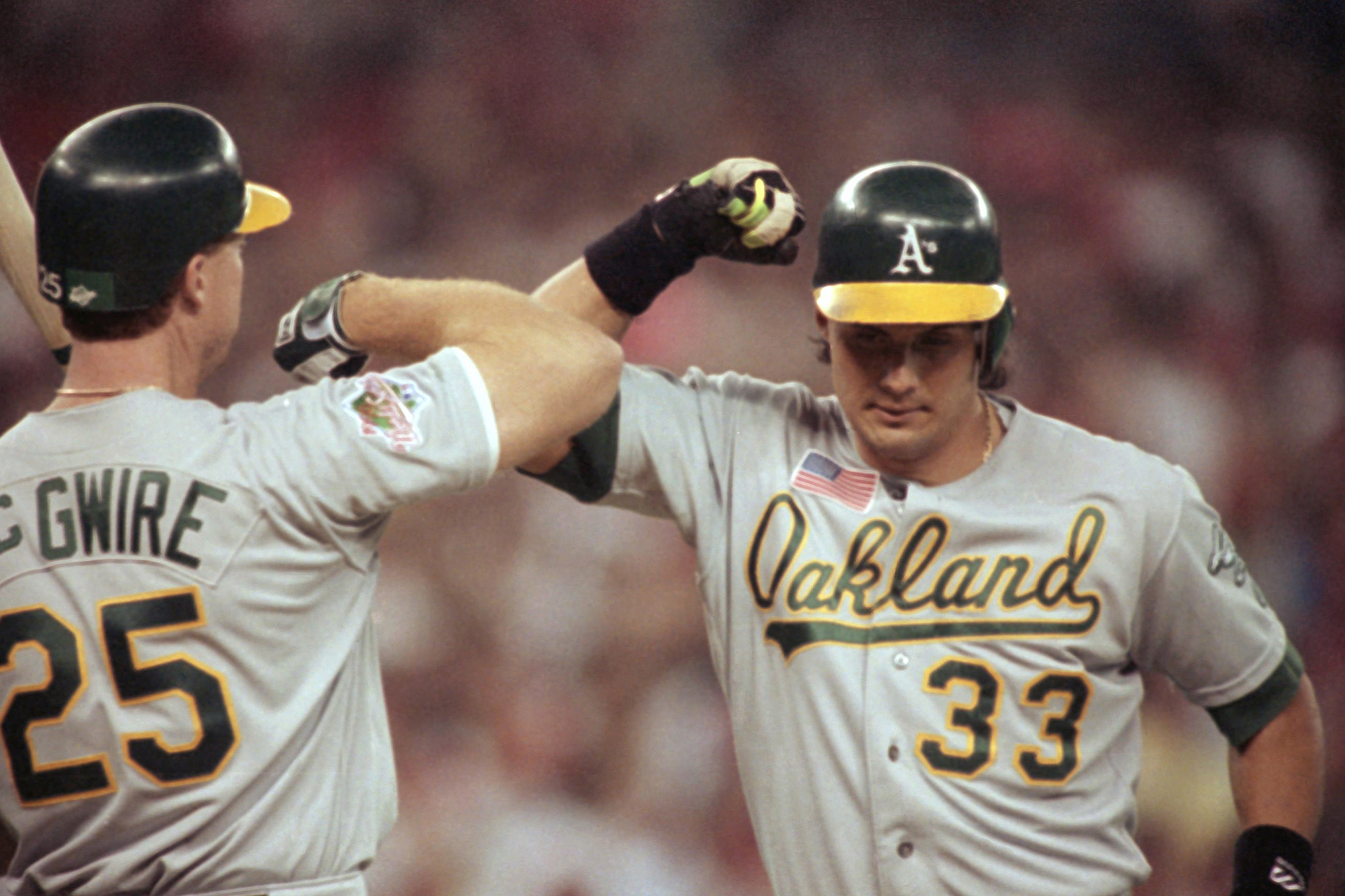 Oakland Athletics Jose Canseco, right, bashes elbows with teammate Mark McGwire following Cansecos solo homerun in the third inning of game two of the World Series against the Cincinnati Reds, Wednesday, Oct. 17, 1990, Cincinnati, Ohio.
