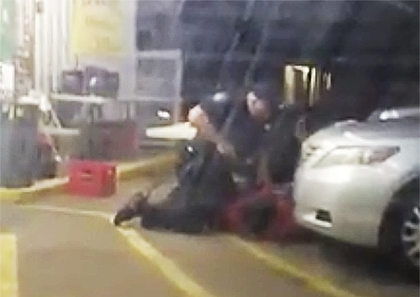 In this Tuesday, July 5, 2016 photo made from video, Alton Sterling is held by two Baton Rouge police officers, with one holding a hand gun, outside a convenience store in Baton Rouge, La. Moments later, one of the officers shot and killed Sterling, a black man who had been selling CDs outside the store, while he was on the ground.