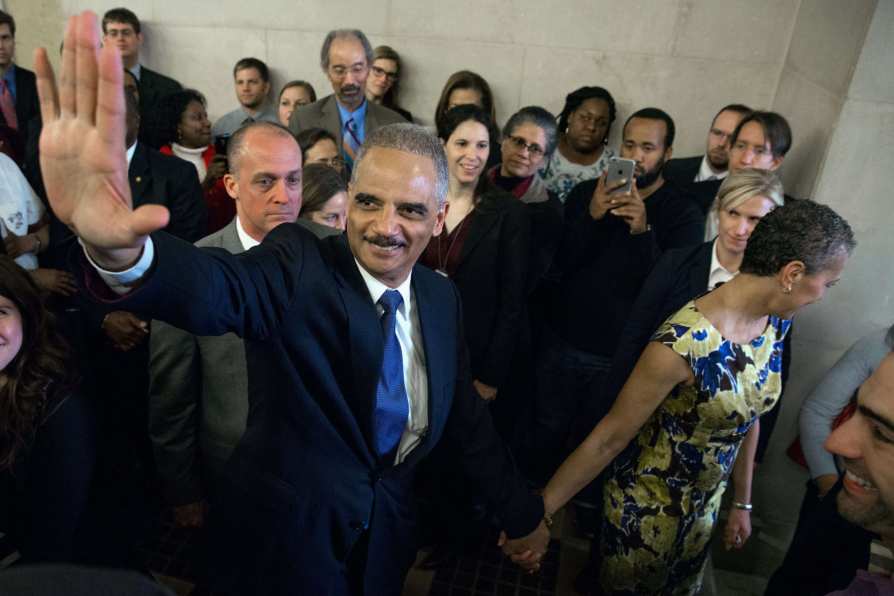 U.S. Attorney General Eric Holder says goodbye to Justice Department employees as he leaves the Robert F. Kennedy building with his wife April 24, 2015 in Washington, DC.
