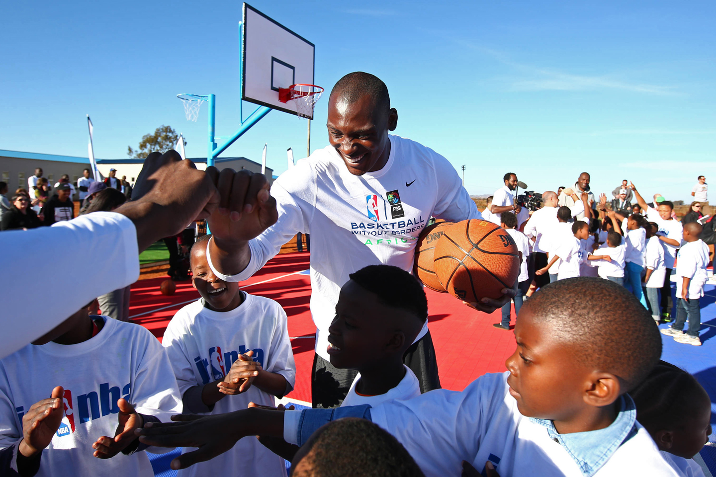 Bismack Biyombo #8 of the Toronto Raptors shakes kids hands during the Boys & Girls Club of Protea Glen court dedication as part the Basketball Without Boarders program on July 30, 2015 at the Protea Glen Clubhouse in Soweto, South Africa.