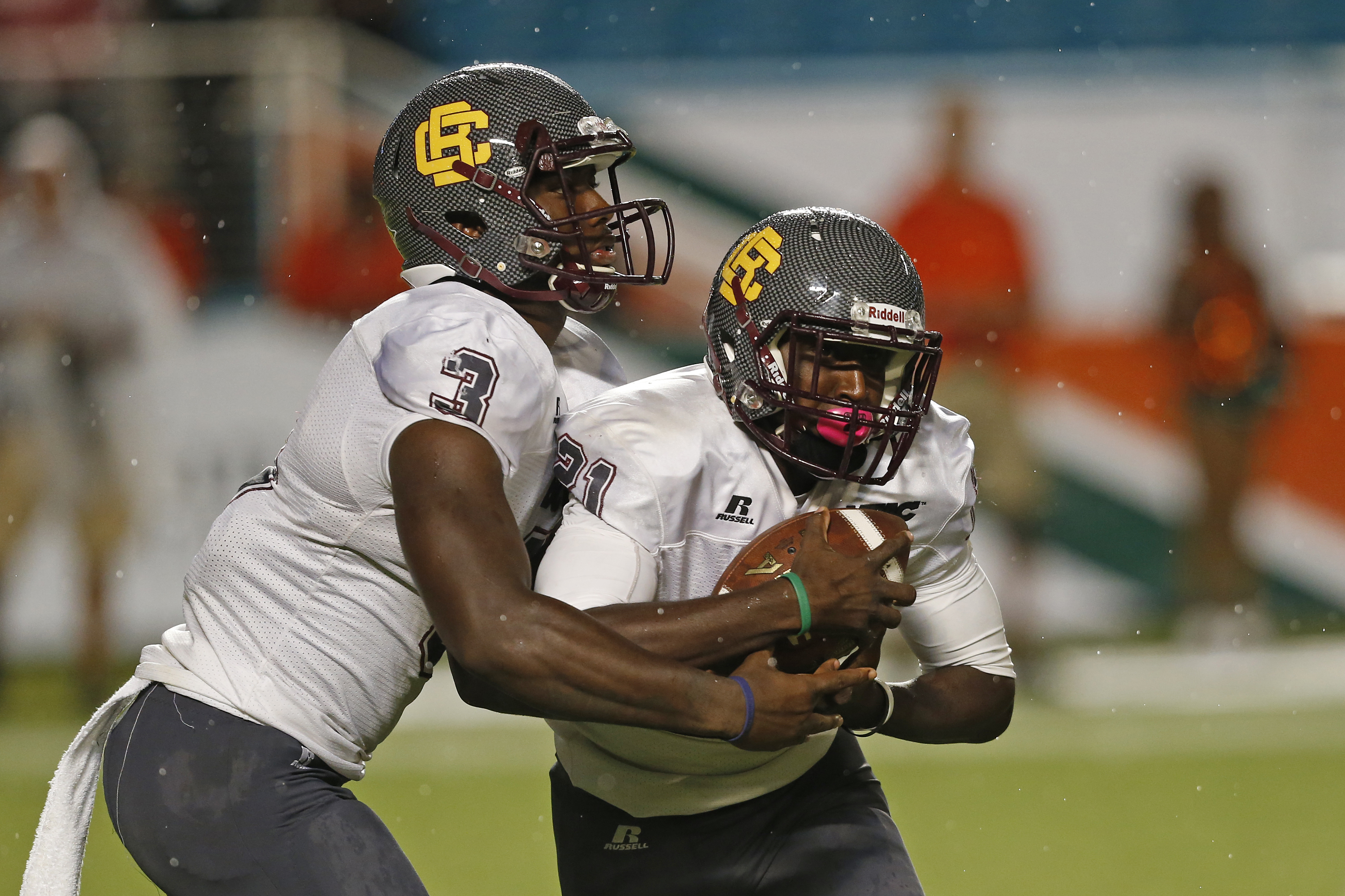 Quentin Williams #3 hands the ball off to Michael Jones #21 of the Bethune-Cookman Wildcats during second quarter action against the Miami Hurricanes on September 5, 2015 at Sun Life Stadium in Miami Gardens, Florida.