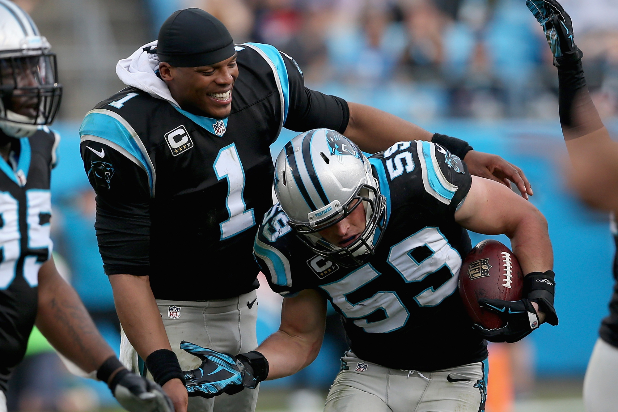 Cam Newton #1 congratulates teammate Luke Kuechly #59 of the Carolina Panthers after Kuechly made an interception in the 3rd quarter during their game against the Atlanta Falcons at Bank of America Stadium on December 13, 2015 in Charlotte, North Carolina.
