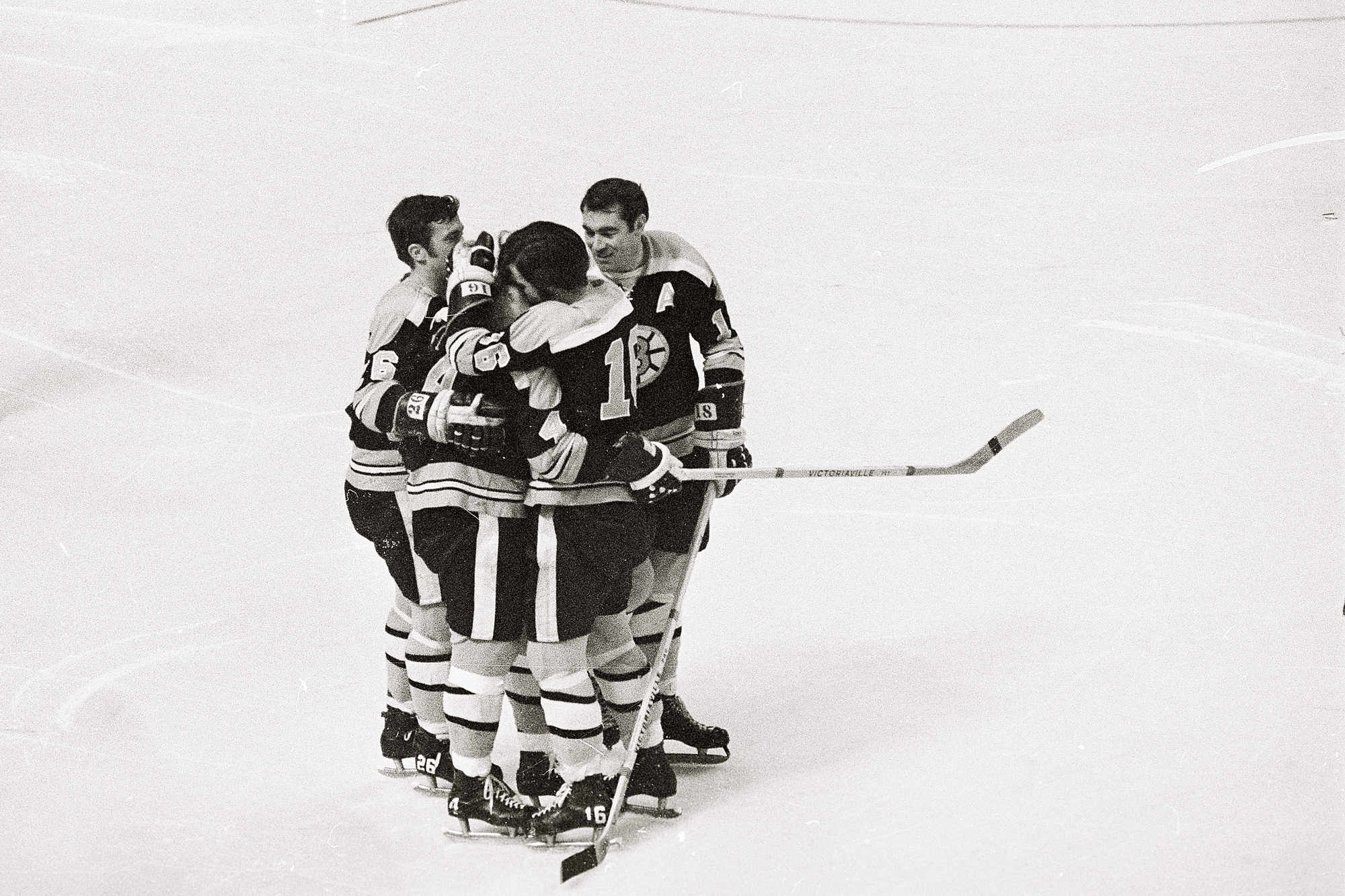 Bruin's Bobby Orr (4) is embraced by teammates Don Awrey (26), Derek Sanderson, (16), and Ed Westfall, (18), after Orr became the first defense man in NHL history to score 100 points on a goal during the 2nd period of the game on March 15th. Orr boosted his total to a league leading 101, as he scored two goals and two assists. The game ended in a 5-5 tie.