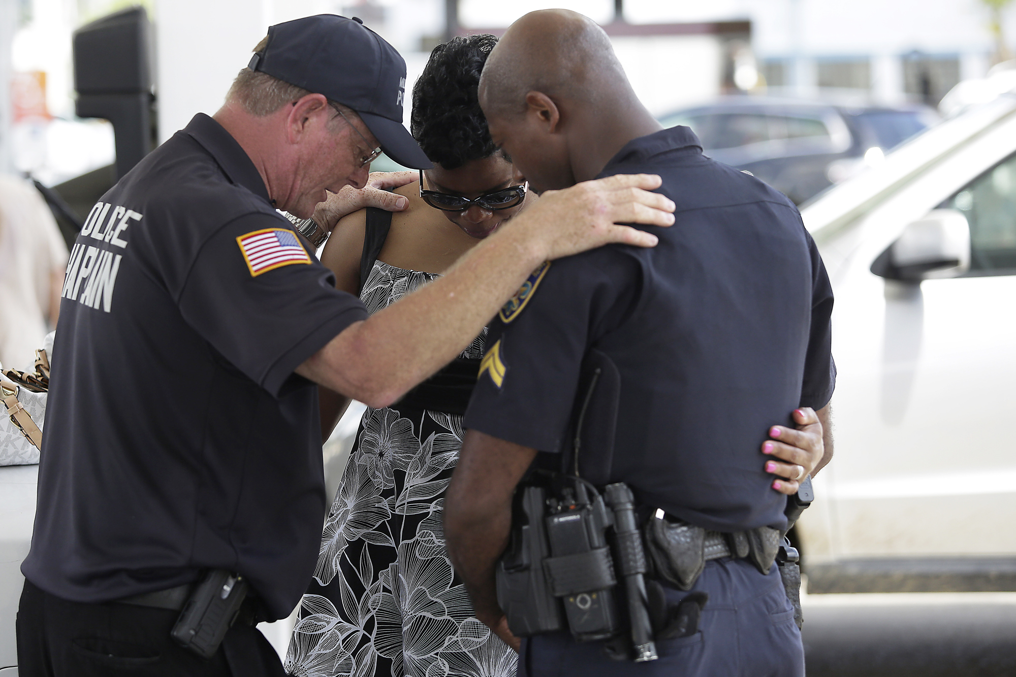 Millville, New Jersey police chaplain Bob Ossler (L) prays with Baton Rouge Police Department Corporal Trina Dorsey (C) and her brother Corporal Joseph Keller near a makeshift memorial for three police officers on July 19, 2016 in Baton Rouge, Louisiana.