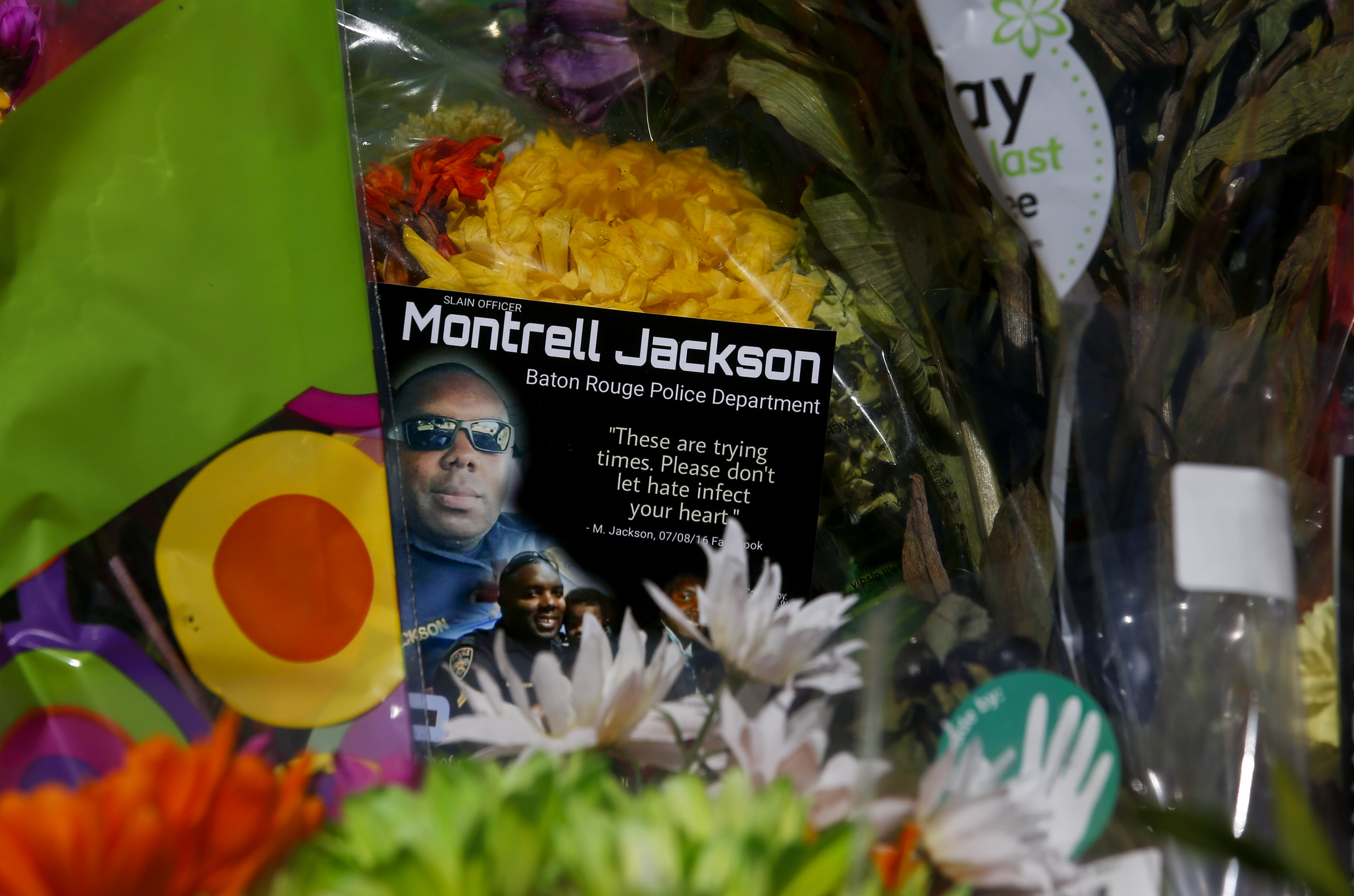 A photo card of one of the three slain Baton Rouge police officers, Montrell Jackson, is nestled among the flowers left by the public at the roadside memorial on July 19, 2016 in Baton Rouge, Louisiana.