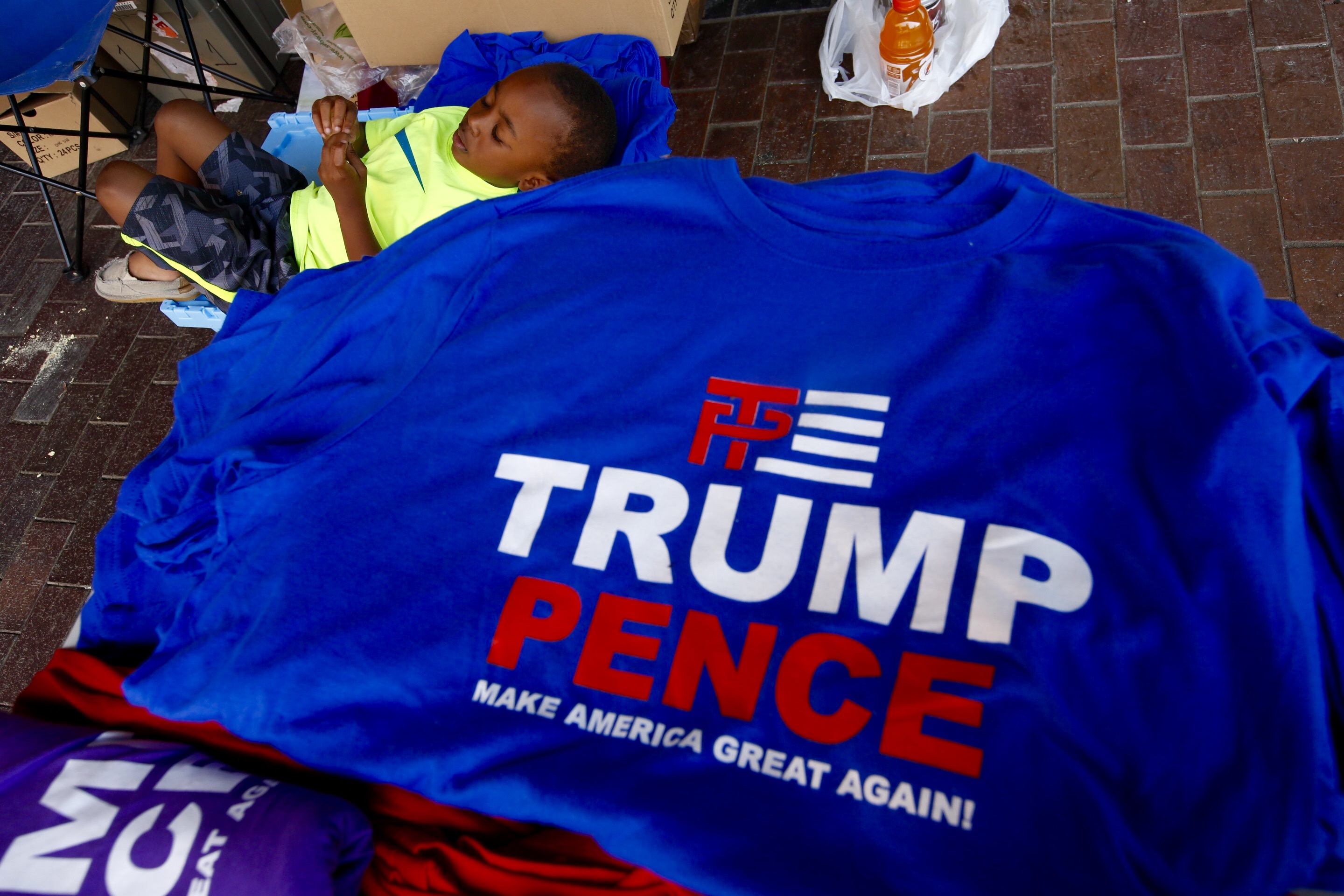 Brighton Williams , age 4, of South Carolina waits as his father Shawn Williams sells Trump t-shirts and buttons in downtown Cleveland Tuesday, July 19, 2016.