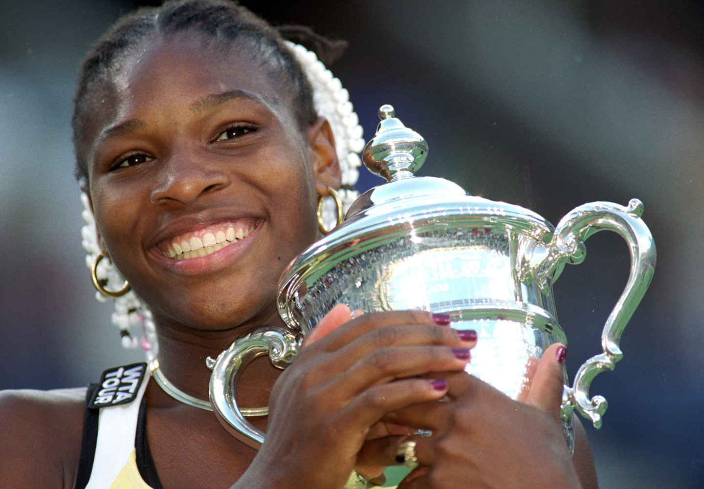A close up of Serena Williams of the USA as she poses with her trophy after the match between Martina Hingis of Switzerland in the US Open at the USTA National Tennis Center in Flushing Meadows, New York. Williams defeated Hingis 6-3, 7-6 (7-4).