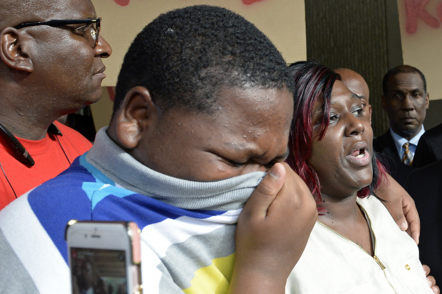 Cameron Sterling, left, Alton Sterling's son, cries, as his mother Quinyetta McMillan speaks about the shooting of Alton Sterling during a press conference and protest at city hall Wednesday, July 6, 2016.