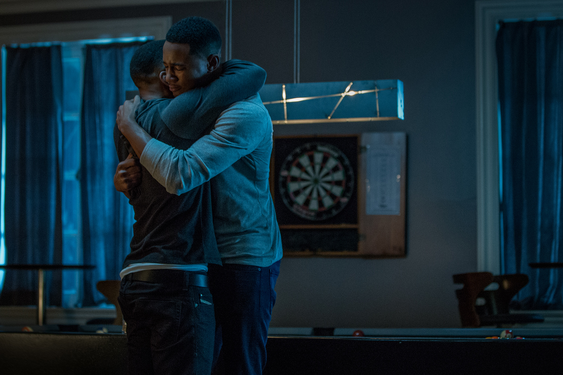 Reggie (RonReaco Lee) and Cam (Jessie T. Usher) share an embrace as they grieve the loss of Uncle Julius.