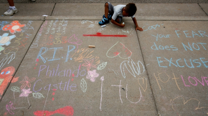 A boy sits near messages written in chalk as demonstrators protesting the shooting death of Castile gather in front of the police department in St Anthony