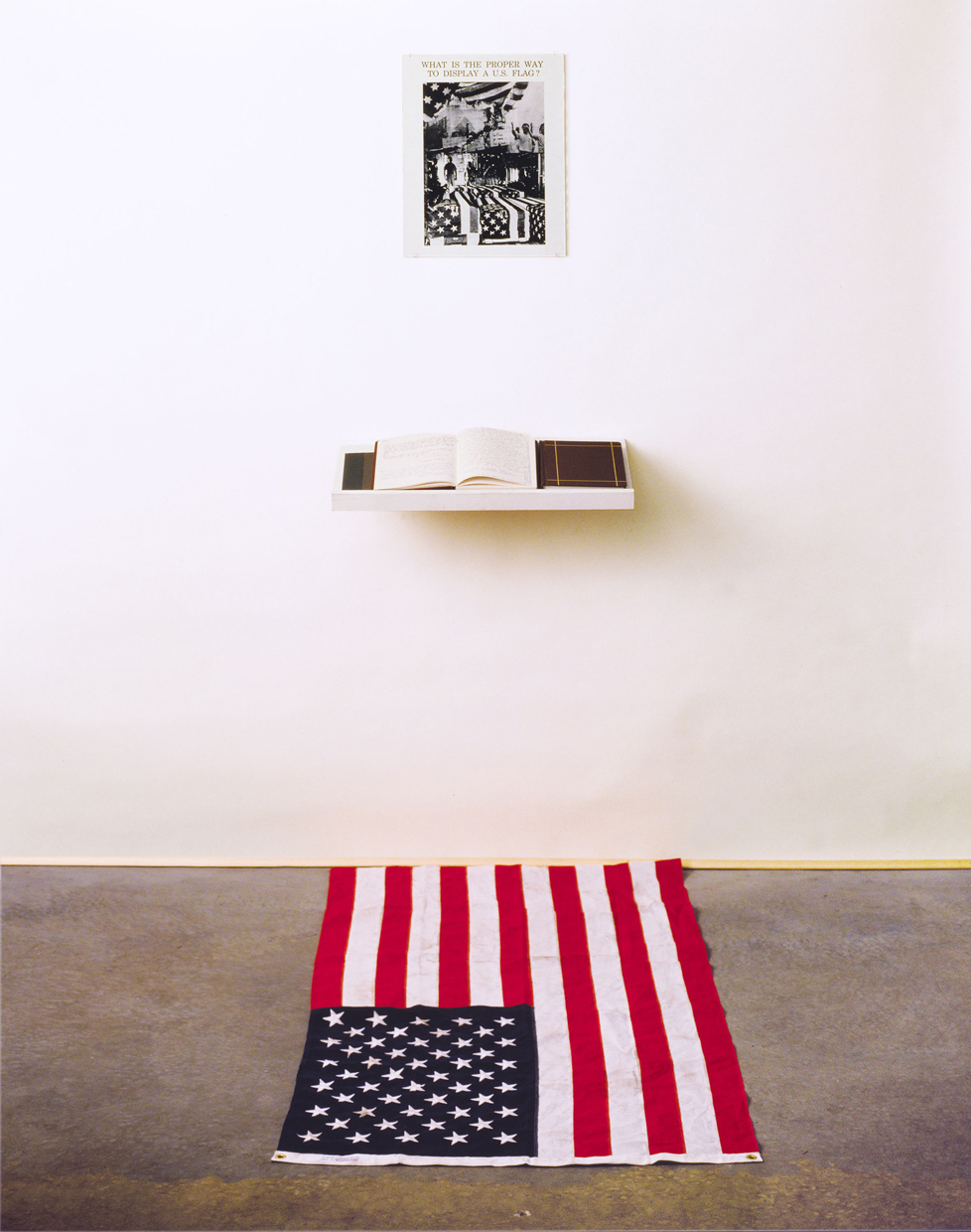 """What is the Proper Way to Display a U.S. Flag?"" Installation: Silver gelatin print, books, pens, shelf, active audience, US flag, 80"" x 28"" x 12"", 1988."